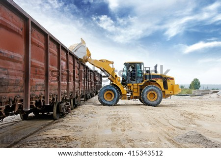 Loader loads the wagon train transport against cloud sky - stock photo