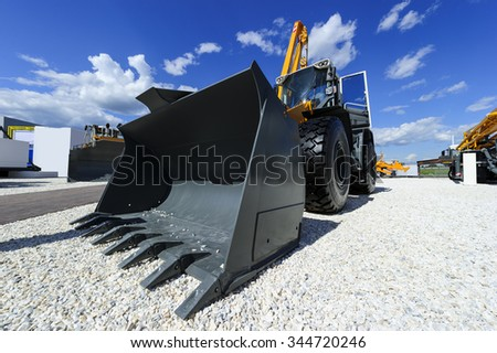 Loader, wheel bulldozer with big grey bucket, construction industry, heavy yellow excavator on building area with gravel, different machinery, blue sky and white clouds on background  - stock photo
