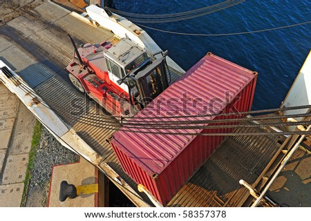loader with container entering the oceanic ferry ship