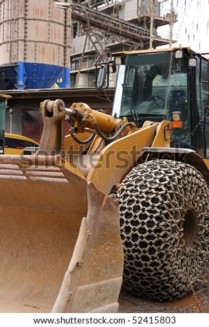 Loader with large wheels and steel chains - stock photo
