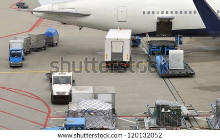 Loading an aeroplane with airfreight at an airport - stock photo