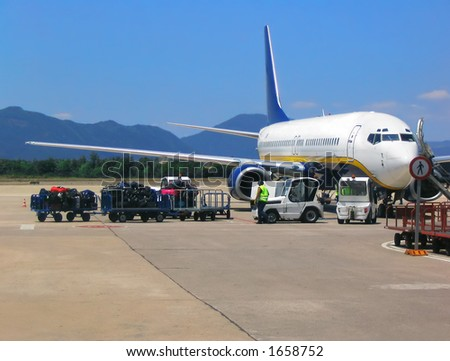 Loading baggage on airplane - stock photo