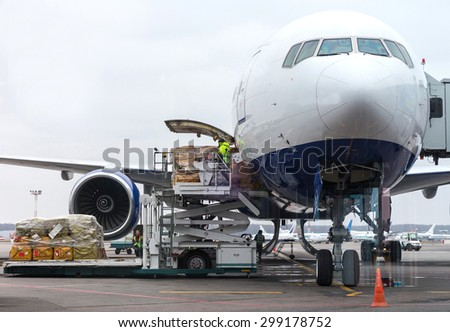 Loading cargo into the aircraft before departure - stock photo