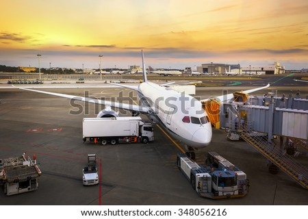 Loading cargo on the plane in airport, view through window - stock photo