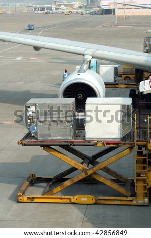 Loading cargo to a commercial airplane - stock photo