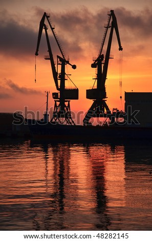 Loading cranes of seaport stand against a decline and the sea