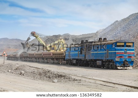 Loading of iron ore on the train in career - stock photo