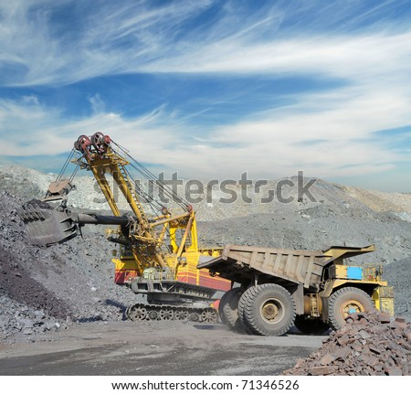 Loading of iron ore on very big dump-body truck - stock photo