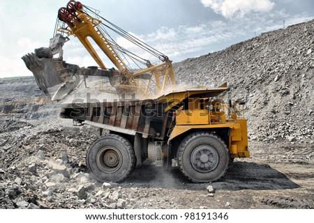 Loading of iron ore on very big dump-body truck - stock photo