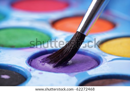 Loading paint brush with paint from a watercolors palette - stock photo
