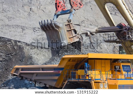 Loading the ore into heavy dump truck at the opencast mining - stock photo