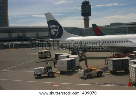 Loading up a plane at Vancouver Airport. Workers are placing baggage and food on the plane - stock photo