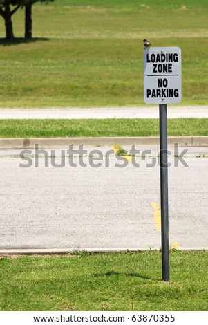 Loading Zone A bird sits on a Loading Zone-No Parking sign. Vertical. - stock photo