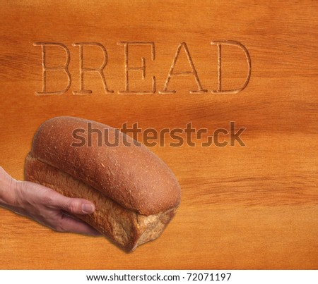 Loaf of  bread against a wooden background. - stock photo