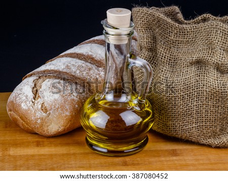 Loaf of bread and bottle of olive oil on a wooden board.