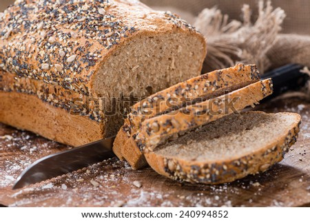 Loaf of bread (fresh baked) on rustic wooden background - stock photo