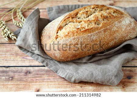 loaf of bread on wooden background, food closeup - stock photo