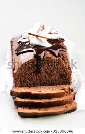 Loaf of chocolate cake with chocolate ganache frosting and coconut pieces - stock photo