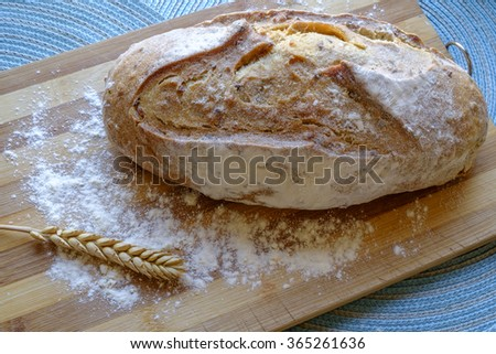 Loaf of fresh bread with seeds with some wheat on a bamboo board in landscape top wide - stock photo