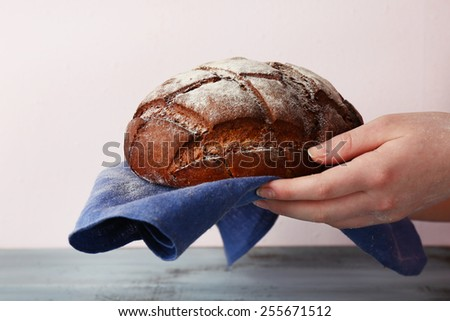 Loaf of freshly bread in female hands with napkin on color wooden table and light background - stock photo