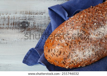 Loaf of freshly bread with napkin on color wooden table background - stock photo
