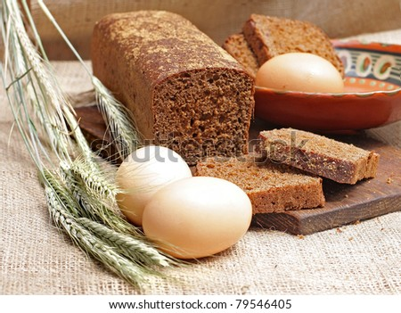 loaf of rye bread and bread slices lie on a linen fabric near to ripe ears and eggs - stock photo