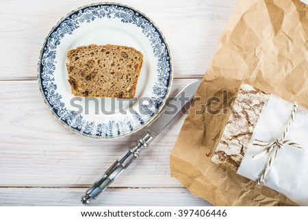 Loaf of rye bread and one slice on a plate - stock photo