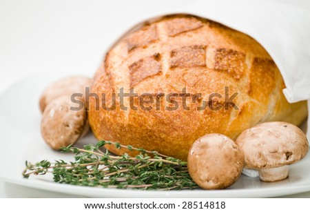 Loaf of sourdough bread with fresh mushrooms and thyme