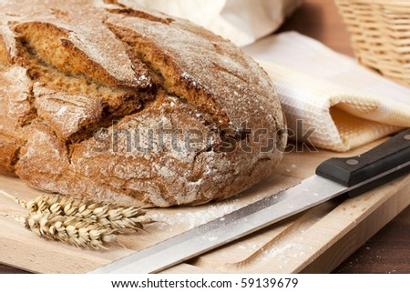 loaf of traditionally baked rustic bread with knife, wheat ears, towel, flour, cutting board