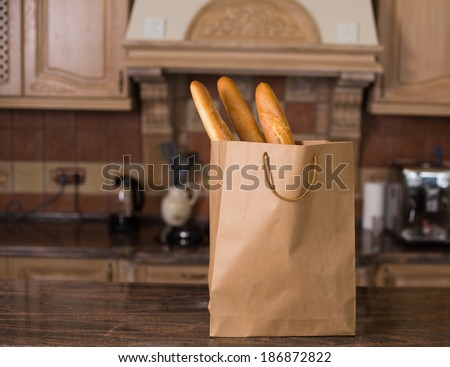Loaf of white bread packaged in a paper bag on the kitchen - stock photo
