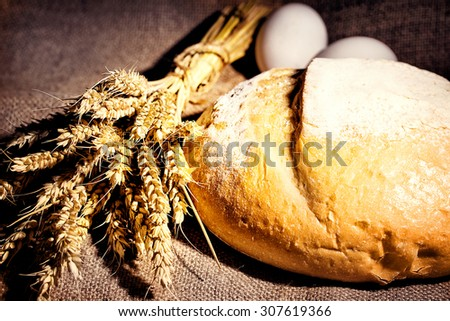 Loaf of white bread with ears and eggs taken from a blurred background