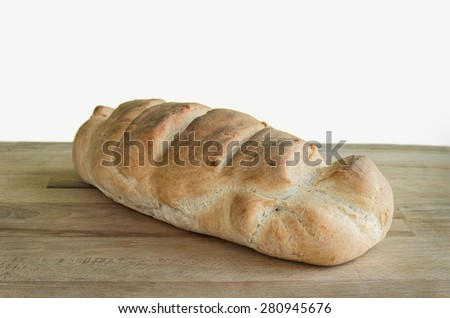 Loaf of whole wheat bread isolated on white. Home made organic crunchy tasty healthy bread sitting on a wooden surface - cutting board. Retro look image - stock photo