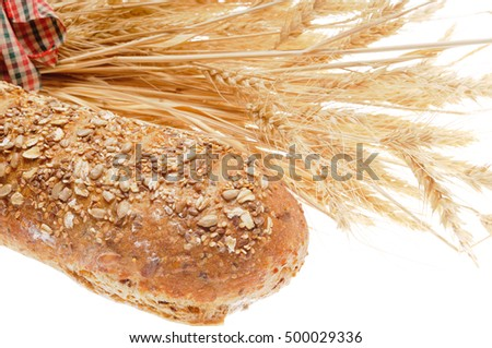 Loaf of whole wheat multi-grain bread in front of a sheaf of wheat tied with a ribbon and isolated on white