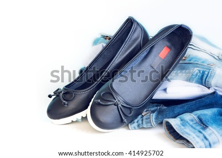 Loafers sleep on female leather blue shoes on white background empty space for text.Jeans clothes & footwear set. - stock photo