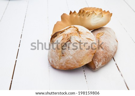 Loafs of bread on a white wood table