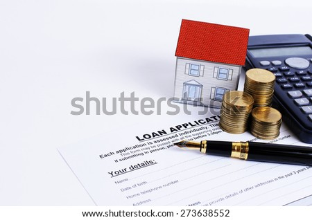 Loan application form and fountain pen and calculator and coins stack and paper house