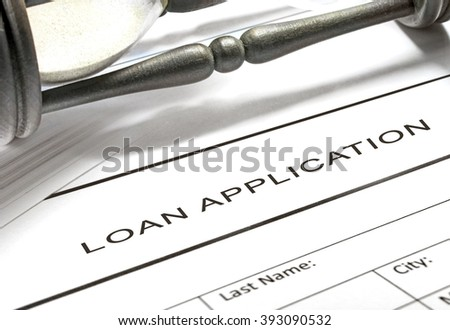 Loan application form with hourglass on background.
