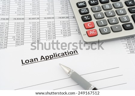 loan application with calculator and pen - stock photo