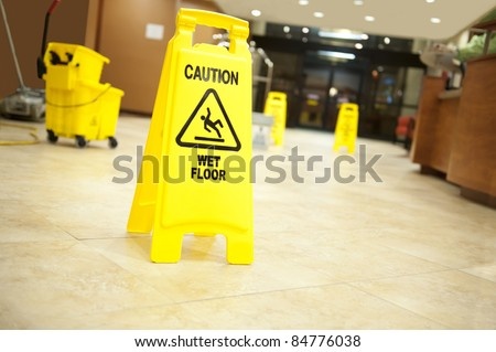 "Lobby floor with mop bucket and ""caution wet floor"" signs, selective focus on nearest sign - stock photo"