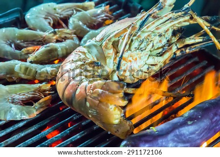 Lobster grilled barbecued seafood in BBQ Flames. - stock photo