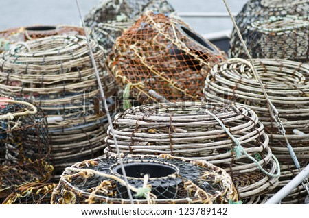 Lobster or crayfish pots stacked on fishing boat, close focus on centre pot, St Helens, Tasmania, Australia - stock photo