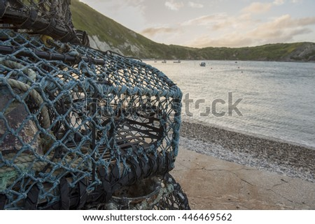 Lobster pot with Lulworth cove on the Jurassic coast of Dorset blurred background, on a summer morning.  - stock photo
