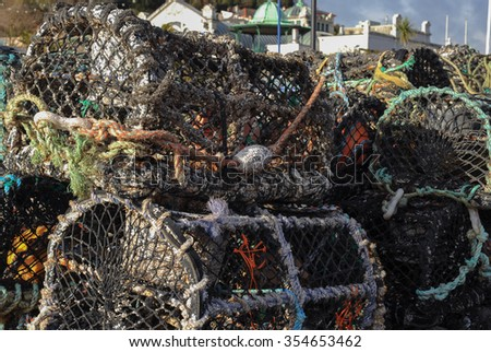 Lobster Pots on the Quayside in the Harbour of the Holiday Resort of Torquay on the East Coast of Devon, England, UK - stock photo