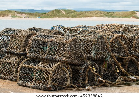 Lobster pots stacked in pile on a harbour with a sandy bay in the background