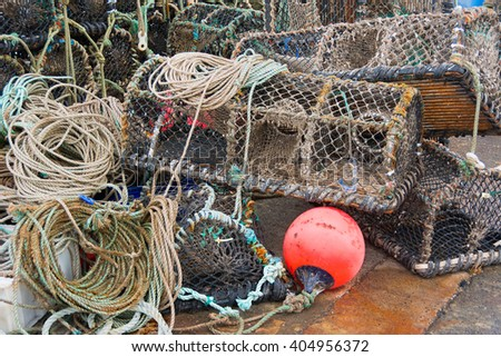 Lobster pots stacked on quayside forming a pattern - stock photo