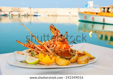 Lobster served with vegetables on white plate. Rethymno, Crete, Greece - stock photo
