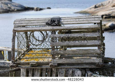 Lobster trap with Peggys Cove harbour in background - stock photo
