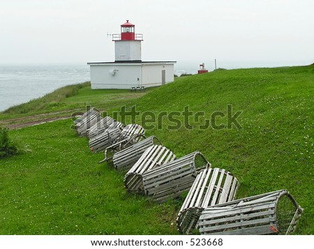 lobster traps sitting on the grass  near a lighthouse in New Brunswick harbor, Canada