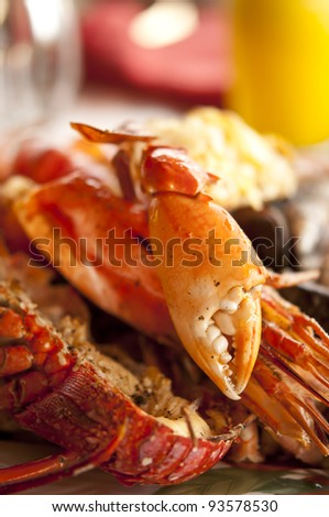 Lobsters and crabs cooked on dinner dish with selective focus on the crab nipper - stock photo