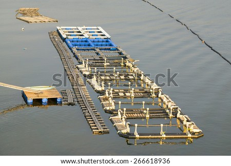 Local popular Asian fish farm cage for sustainable fish supply. - stock photo